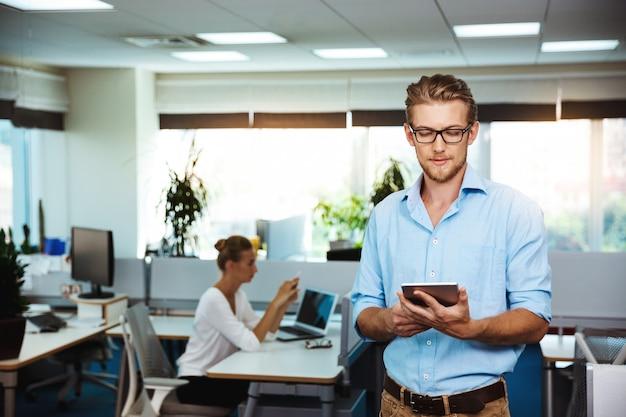 Giovane imprenditore di successo sorridente, guardando tablet, oltre ufficio