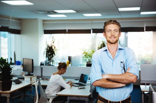 Giovane imprenditore di successo sorridente, in posa con le braccia incrociate, sopra l'ufficio