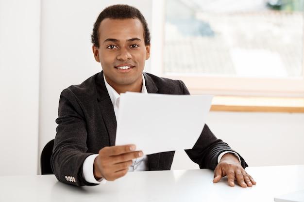 Giovane imprenditore di successo sorridente, in possesso di carta, seduto sul posto di lavoro