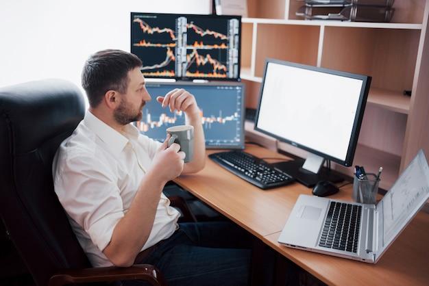 Giovane imprenditore è seduto in ufficio al tavolo, lavorando sul computer con molti monitor, diagrammi sul monitor. l'agente di borsa analizza i grafici delle opzioni binarie uomo dei pantaloni a vita bassa che beve caffè, studiando