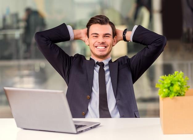 Giovane imprenditore felice con scatole e laptop.