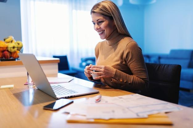 Giovane imprenditore femminile biondo sorridente attraente seduto a casa, bevendo caffè e guardando il laptop durante la quarantena del virus corona.