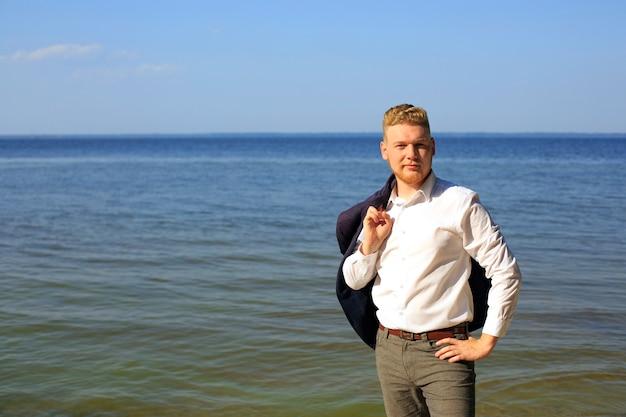 Giovane imprenditore in una camicia bianca e con una giacca in piedi vicino al mare
