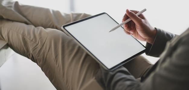 Giovane imprenditore lavorando sul suo progetto durante la scrittura su tablet schermo vuoto