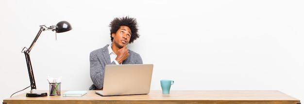 Giovane imprenditore nero pensando, sentendosi dubbioso e confuso, con diverse opzioni, chiedendosi quale decisione prendere su una scrivania