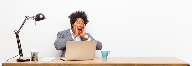 Giovane imprenditore nero sentirsi felici, eccitati e sorpresi, guardando al lato con entrambe le mani sul viso su una scrivania