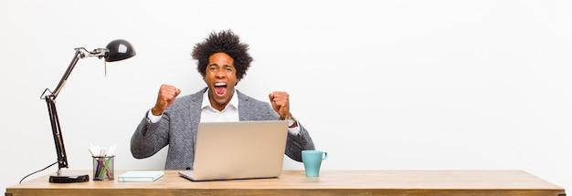 Giovane imprenditore nero sentirsi felici, sorpresi e orgogliosi, gridando e celebrando il successo con un grande sorriso su una scrivania