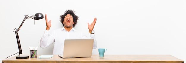 Giovane imprenditore nero sentirsi felici, stupiti, fortunati e sorpresi, celebrando la vittoria con entrambe le mani in alto su una scrivania