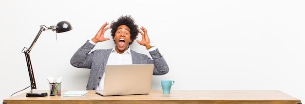 Giovane imprenditore nero urlando con le mani in alto nell'aria, sentendosi furioso, frustrato, stressato e sconvolto su una scrivania