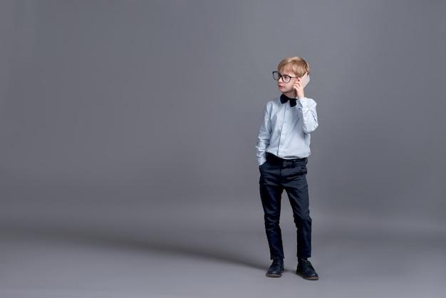 Giovane imprenditore parlando al telefono. ragazzino che posa su un gray