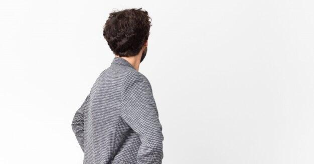 Giovane imprenditore pazzo sentirsi confuso o pieno o dubbi e domande, chiedendosi, con le mani sui fianchi, vista posteriore contro il muro