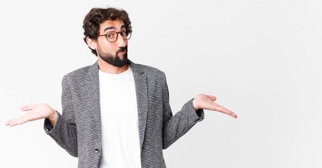 Giovane imprenditore pazzo sentirsi perplesso e confuso, dubitando, ponderando o scegliendo diverse opzioni con espressione divertente contro la parete piatta