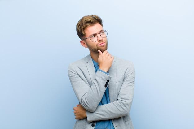 Giovane imprenditore pensando, sentendosi dubbioso e confuso, con diverse opzioni, chiedendosi quale decisione prendere contro il blu