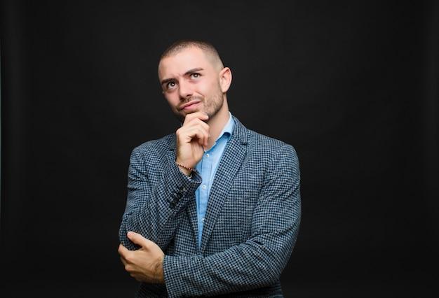 Giovane imprenditore pensando, sentendosi dubbioso e confuso, con diverse opzioni, chiedendosi quale decisione prendere oltre il muro