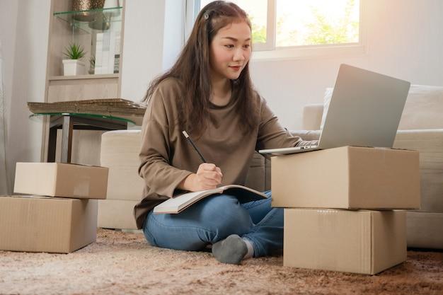 Giovane imprenditore, seduto sul pavimento e lavorando a casa.
