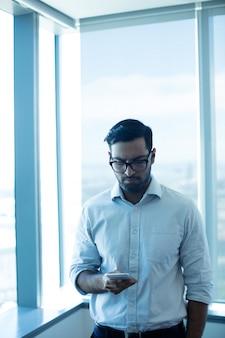 Giovane imprenditore utilizzando il telefono cellulare mentre in piedi contro la finestra di vetro