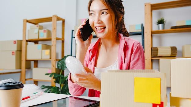 Giovane imprenditrice asia utilizzando la chiamata del telefono cellulare che riceve l'ordine di acquisto e controlla il prodotto in magazzino, lavora in ufficio a casa. proprietario di una piccola impresa, consegna sul mercato online, concetto di freelance di stile di vita.