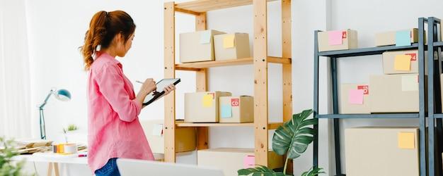 Giovane imprenditrice asiatica imprenditrice controlla l'ordine di acquisto del prodotto in magazzino e salva sul tablet che lavora in ufficio a casa. proprietario di una piccola impresa, consegna sul mercato online, concetto di freelance di stile di vita.