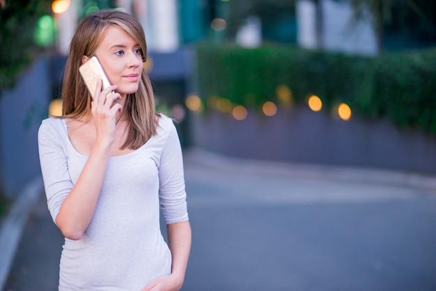 Giovane imprenditrice avendo una conversazione utilizzando uno smartphone su una telefonata
