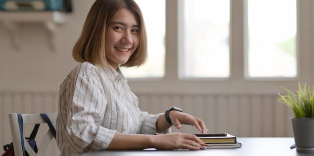 Giovane imprenditrice bella lavorando sul suo progetto con lo smartphone