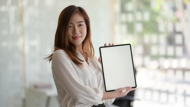 Giovane imprenditrice bella mostrando tablet schermo vuoto