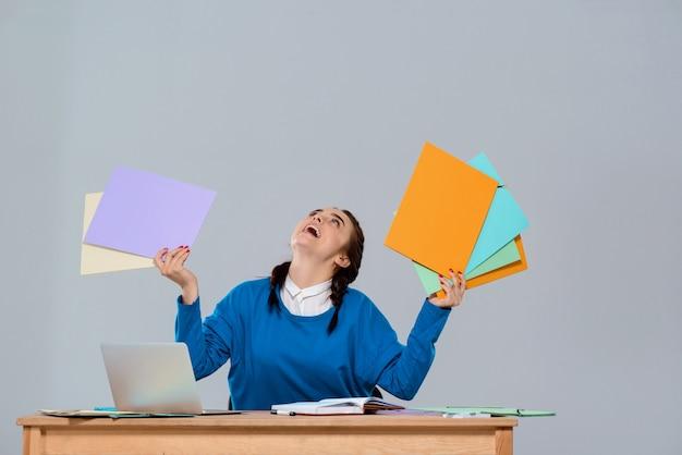 Giovane imprenditrice bella seduta sul posto di lavoro, con cartelle colorate