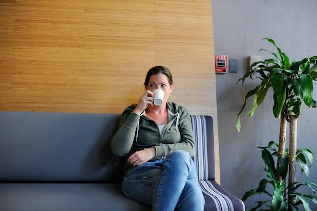 Giovane imprenditrice bere caffè durante la pausa ufficio
