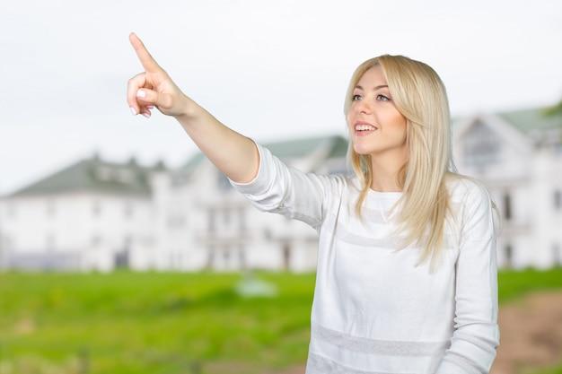Giovane imprenditrice bionda premendo il pulsante touchscreen