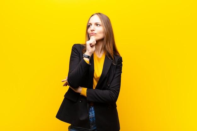 Giovane imprenditrice carina pensando, sentendosi dubbiosa e confusa, con diverse opzioni, chiedendosi quale decisione prendere contro la parete arancione