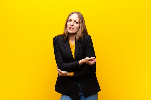 Giovane imprenditrice carina sentirsi ansiosa, malata, malata e infelice, con dolori dolorosi allo stomaco o influenza contro la parete arancione