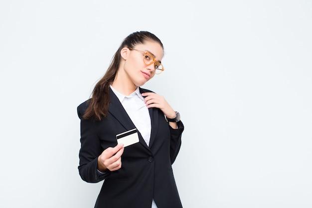 Giovane imprenditrice cercando arrogante, di successo, positivo e orgoglioso, che punta a sé con le banconote con le bollette