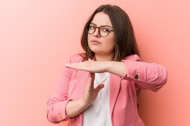 Giovane imprenditrice che mostra un gesto di timeout
