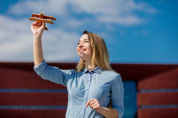 Giovane imprenditrice con piano in legno giocattolo