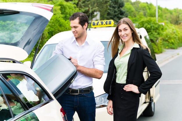 Giovane imprenditrice di fronte al taxi con i bagagli