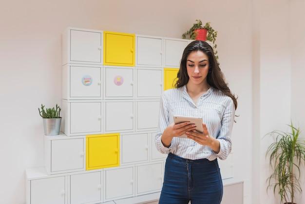 Giovane imprenditrice di lavoro con la sua tavoletta in ufficio