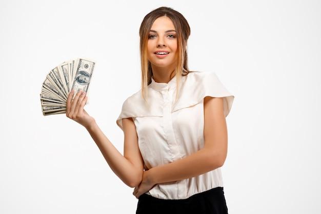 Giovane imprenditrice di successo in possesso di denaro su sfondo bianco.