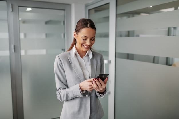 Giovane imprenditrice indoeuropea positiva in tuta in piedi all'interno dell'azienda aziendale e utilizzando smart phone per leggere un messaggio di posta elettronica.