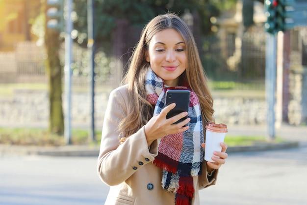 Giovane imprenditrice indossando cappotto e sciarpa a piedi in una strada cittadina