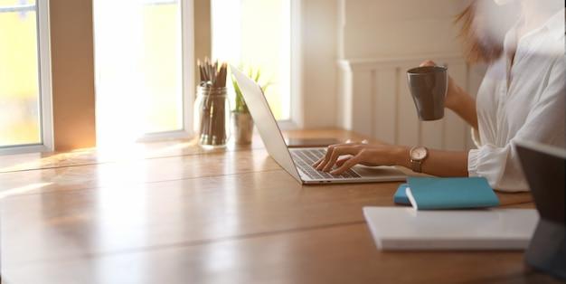 Giovane imprenditrice lavorando con un computer portatile e bevendo una tazza di caffè