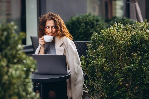 Giovane imprenditrice lavorando su un computer fuori dal bar