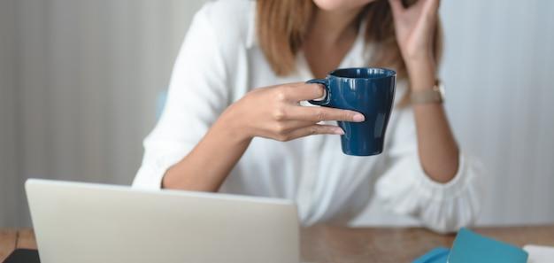 Giovane imprenditrice lavorando sul suo progetto e bere una tazza di caffè in ufficio moderno