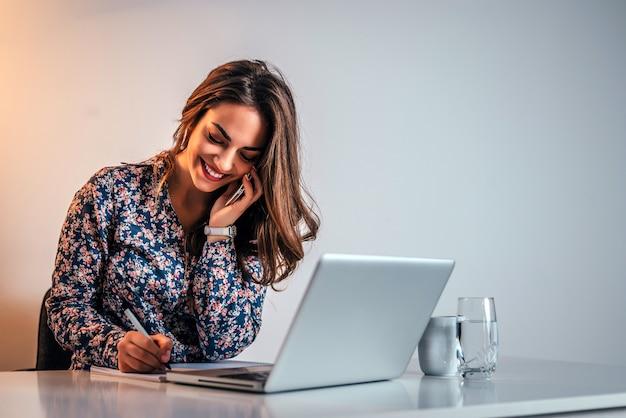 Giovane imprenditrice parlando al telefono in ufficio e prendere appunti.