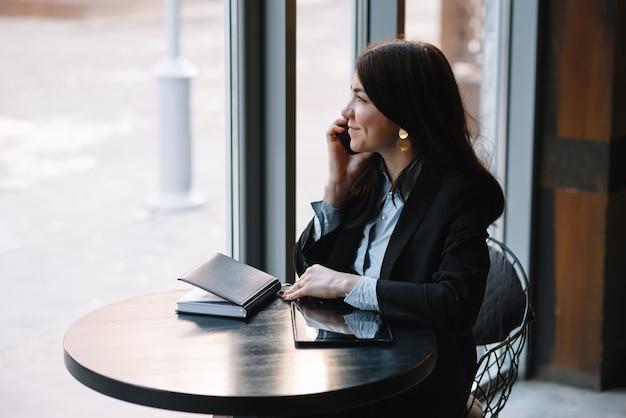 Giovane imprenditrice parlando al telefono nella caffetteria