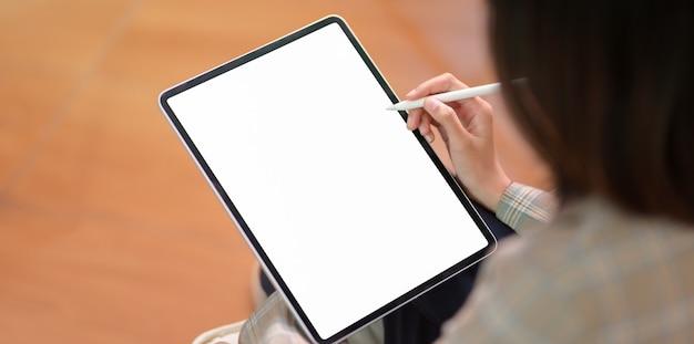 Giovane imprenditrice scrivendo su tablet schermo vuoto