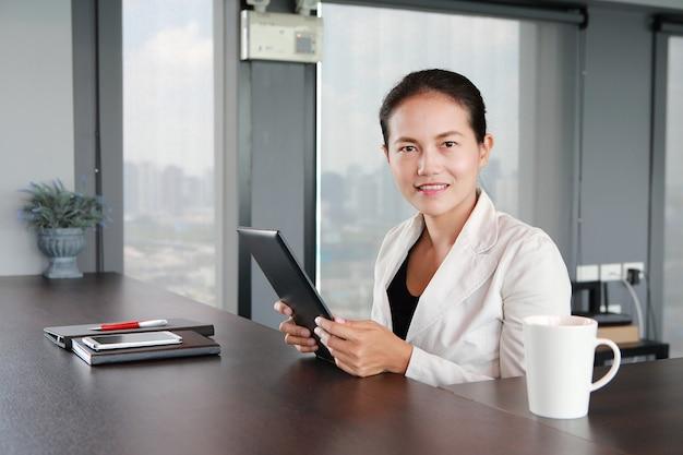 Giovane imprenditrice seduto al tavolo sul posto di lavoro in ufficio con il gioco di tablet