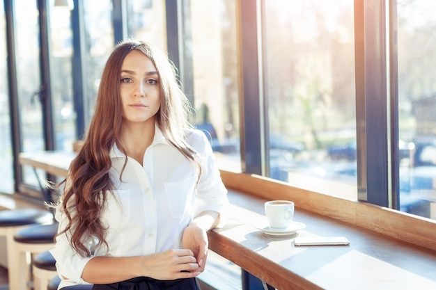Giovane imprenditrice sorridente attraente bere caffè in un caffè