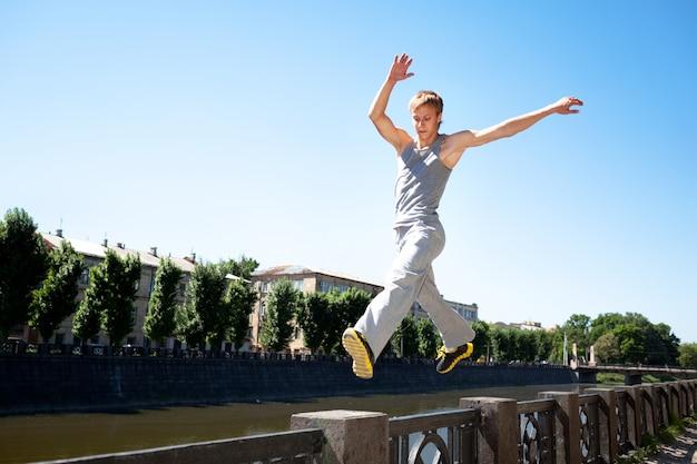 Giovane in abiti sportivi che saltano e che praticano parkour fuori sul recinto di pietra sopra l'argine del fiume il chiaro giorno di estate