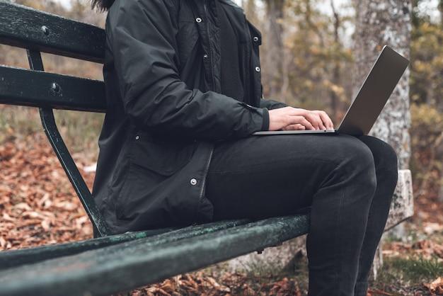 Giovane in autunno parco. uomo indipendente che lavora al suo computer portatile che si siede su un banco nel parco. studente che si prepara per gli esami all'aperto utilizzando un computer portatile.