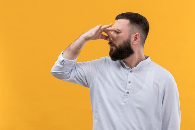 Giovane in camicia bianca con la barba che copre il naso a causa dell'odore