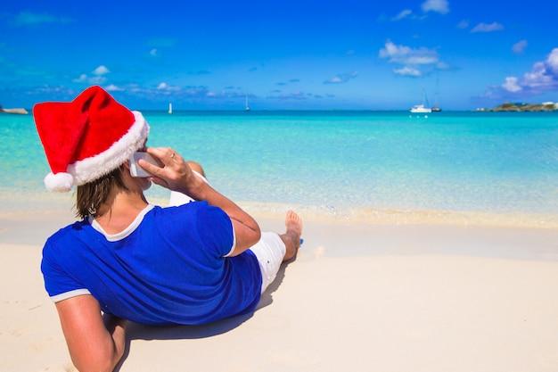 Giovane in cappello di santa che parla sul telefono alla spiaggia tropicale